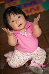 Central America, Guatemala, baby girl on floor.  MR