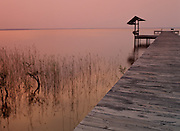 A long pier sits on a calm lake, the sunset turning the water and sky hues of red
