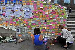 People leave messages of support on the base of the obelisk on London Bridge, after an unknown 21 year-old man left a box of tape, sticky notes and marker pens with an invite to write a message, following the terror attack in which eight people died.