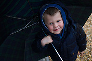 A 4 year-old boy holds an umbrella outdoors in family woods. Before he and his parents take a stroll through local woods, the boy wears a warm coat and a hood over his head on this wet, rainy spring day. Smiling at another person, the youngster looks forward to his walk in the great outdoors.