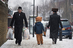 © Licensed to London News Pictures. 01/03/2018. London, UK. An orthodox Jewish child in fancy dress walks with his father through the streets of Stamford Hill in North London during celebrations for the festival of Purim, on March 1, 2018. Purim celebrates the miraculous salvation of the Jews from a genocidal plot in ancient Persia, an event documented in the Book of Esther. Traditionally the jewish community wear fancy dress and exchange reciprocal gifts of food and drink. Photo credit: Ben Cawthra/LNP