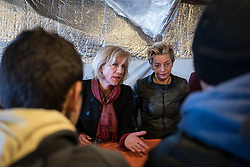 © London News Pictures. Calais, France. 04/03/16. Actress Juliet Stevenson (left) and Producer Tracey Seaward (right) talk with four unaccompanied Syrian boys who live in the Calais 'Jungle' camp and have family in Britain. They are the first celebrities to join the Citizens UK and Help Refugees 'buddy scheme' which aims to put pressure on the British government to allow unaccompanied minors in the Calais 'Jungle' to be reunited with their families in the United Kingdom. Photo credit: Rob Pinney/LNP