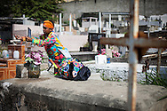 Un integrante de los Diablos coloca una cinta de color sobre la tumba de un familiar durante la festividad del Corpus Christi, representada en Venezuela a traves del ritual magico-religioso de los Diablos Danzantes. Los Diablos de Naiguata se identifican por pintar sus propios trajes y decorarlos con cruces, rayas y circulos, figuras que impiden que el maligno los domine. Las mascaras son en su gran mayoria animales marinos. Llevan escapularios cruzados, crucifijos y cruces de palma bendita. Naiguata, 30 Mayo 2013. (ivan gonzalez)