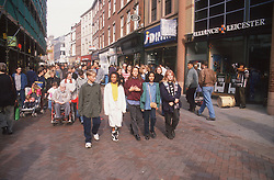 Multiracial group of teenagers walking together through city centre,