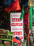 "06 AUGUST 2015 - KATHMANDU, NEPAL: A sign announcing an ""Earthquake Sale"" at a store that sells hiking and trekking supplies to tourists in Kathmandu. Tourism, which accounts for about 8% of the Nepal economy, has virtually collapsed since the earthquake in April causing more damage to the Nepali economy. The areas most heavily damaged, historic sites in the Kathmandu valley and trekking trails in the Himalaya Mountains, are the most popular tourist areas and the earthquake struck in the middle of the tourist high season. The Nepal Earthquake on April 25, 2015, (also known as the Gorkha earthquake) killed more than 9,000 people and injured more than 23,000. It had a magnitude of 7.8. The epicenter was east of the district of Lamjung, and its hypocenter was at a depth of approximately 15 km (9.3 mi). It was the worst natural disaster to strike Nepal since the 1934 Nepal–Bihar earthquake. The earthquake triggered an avalanche on Mount Everest, killing at least 19. The earthquake also set off an avalanche in the Langtang valley, where 250 people were reported missing. Hundreds of thousands of people were made homeless with entire villages flattened across many districts of the country. Centuries-old buildings were destroyed at UNESCO World Heritage sites in the Kathmandu Valley, including some at the Kathmandu Durbar Square, the Patan Durbar Squar, the Bhaktapur Durbar Square, the Changu Narayan Temple and the Swayambhunath Stupa. Geophysicists and other experts had warned for decades that Nepal was vulnerable to a deadly earthquake, particularly because of its geology, urbanization, and architecture.     PHOTO BY JACK KURTZ"