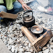 A group of young men in their 20's from Syria and Iraq are making morning tea and boiled eggs at a  disused railway line near the transit camp of Idomeni. Many people decided to live away from the transit camp where the conditions are appalling. <br /> <br /> Thousands of refugees are stranded in Idomeni unable to cross the border. The facilities here are stretched to the limit and the conditions are appalling. It's raining, it's cold there is mud everywhere and there is no hope that the border will open anytime soon.