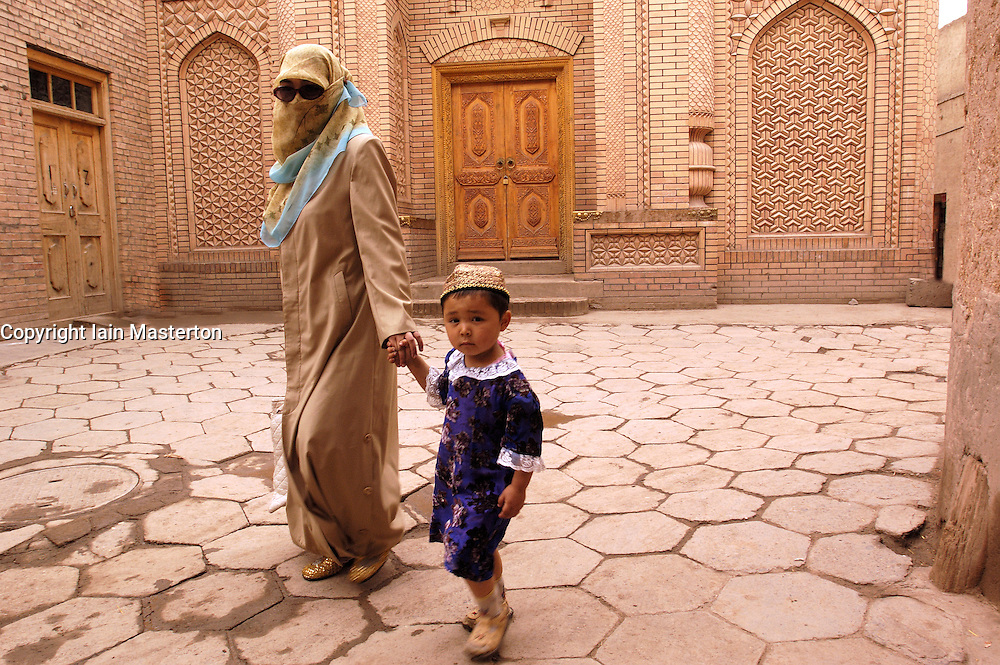 Veiled Uighur mother walking with child in streets of old town in Kashgar in Xinjiang Province China