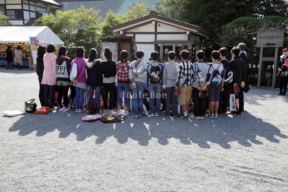 group Japanese school children posing for photo at historical site in kamakura Japan