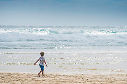 A young boy plays on Fistral Beach in Newquay, Cornwall.