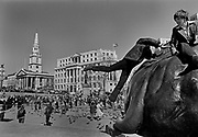 Boy jumping onto lion statue, Trafalgar Square, London. Trafalgar Square is a public space and tourist attraction in central London, built around the area formerly known as Charing Cross. It is situated in the City of Westminster. At its centre is Nelson's Column, which is guarded by four lion statues at its base. Coming and Going is a project commissioned by the Museum of London for photographer Barry Lewis in 1976 to document the transport system as it is used by passengers and commuters using public transport by trains, tubes and buses in London, UK.