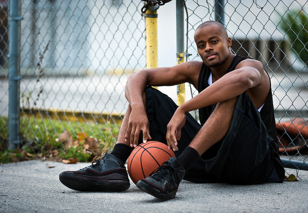 Young basketball player seated in the street looking at camera.