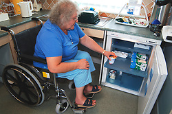 Disabled woman using specially adapted fridge for wheelchair users UK
