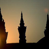 Sunsets over sillhouetted spires of Wat That Luang Temple, Vientiane, Laos