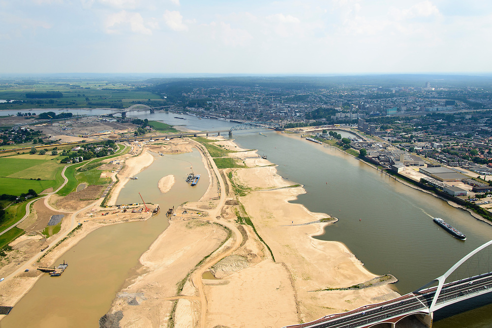 Nederland, Gelderland, Nijmegen, 26-06-2014; onder in beeld de nieuwe stadsbrug van Nijmegen over rivier de Waal, De Oversteek. Daarachter de spoorbrug met fietspad (De Snelbinder) en de laatste brug is de Waalbrug. Links van de rivier grondwerkzaamheden voor de Dijkteruglegging Lent (Ruimte voor de Rivier). Links Nijmegen-Noord, rechts binnenstad.<br /> First bridge the new city bridge of Nijmegen on the river Waal, De Oversteek (The Crossing). Next the railway bridge with cycle path De Snelbinder (The Luggage strap) and finally the Waal bridge. To the left of the river groundwork for the Dike relocation of Lent (project Ruimte voor de Rivier: Room for the River). Nijmegen city on the horizon.<br /> luchtfoto (toeslag op standaard tarieven);<br /> aerial photo (additional fee required);<br /> copyright foto/photo Siebe Swart.