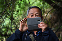 Chinese photographer taking a photo with his mobile phone, Wuliangshan Nature Reserve, Mount Wuliang Nature Reserve in Jingdong county, Yunnan, China.