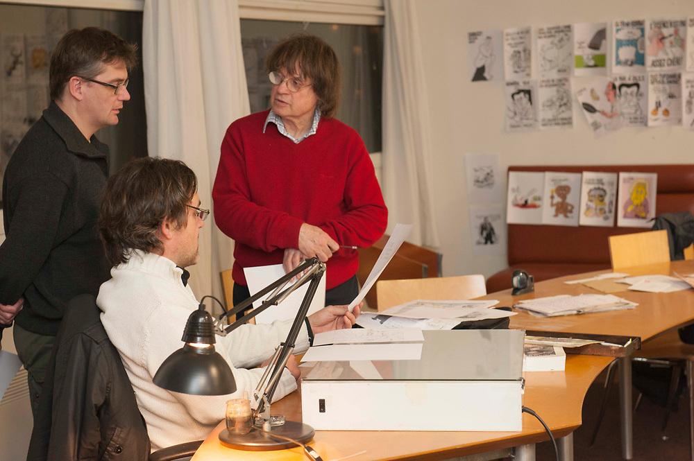 Charb (L), Riss (M) and Cabu (R) talking about the next issue of Charlie Hebdo. The Charlie Hebdo editors  choose the front page for the next issue of Charlie Hebdo among those hanging on the wall, in an office building that was already kept secret after a fire bomb destroyed their former office. Paris, France. January 31, 2012.<br /> Charb (L), Riss (M) et Cabu (R) parlent du prochain numéro de Charlie Hebdo. Les rédacteurs de Charlie Hebdo choisissent la première page du prochain numéro de Charlie Hebdo parmi ceux accrochés au mur, dans un immeuble de bureaux déjà gardé secret après qu'une bombe incendiaire a détruit leur ancien bureau. Paris, France. 31 janvier 2012.