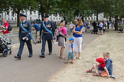 On the 100th anniversary of the Royal Air Force RAF and following a flypast of 100 aircraft formations representing Britains air defence history which flew over central London, two officers walk past playing boys, on 10th July 2018, in London, England.