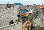 Elevated view of harbour, roofs and tourists climbing walls, Dubrovnik old town, Croatia
