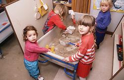 Nursery school children playing with sand in sandpit,