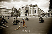A street sweeper at work, with traffic rushing past. Beautifully restored French colonial-era opera house in background.<br /> Ho Chi Minh City (Saigon), Vietnam