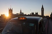 With a setting sun, Big Ben and the Houses of Parliament in the distance, a black London taxi is stopped on Westminster Bridge awaiting a fare, on 29th November 2016, in London, England.