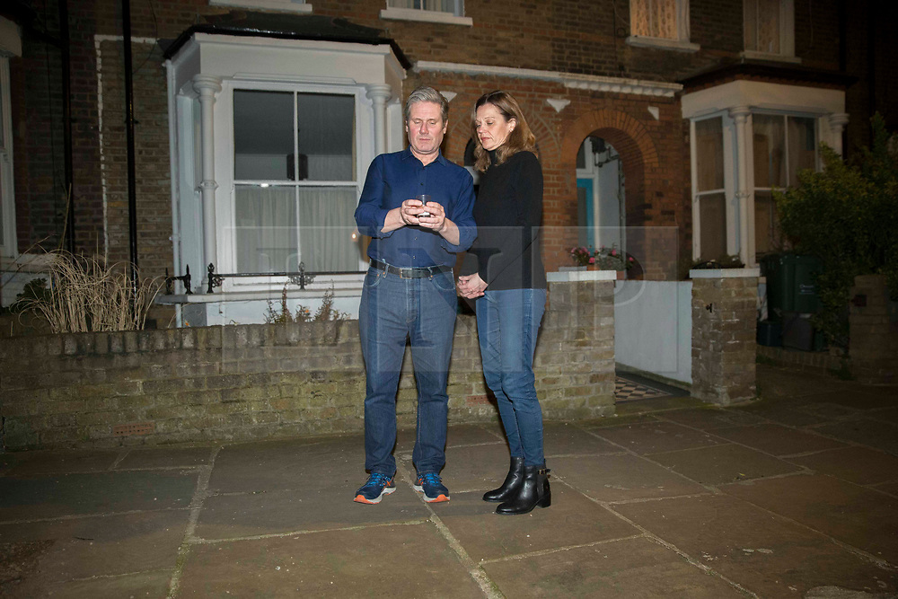 © Licensed to London News Pictures.23/03/2021. Leader of the Labour Party, Sir Keir Starmer with his wife Victoria outside their home in north London join many others across the country on their doorsteps at 8 p.m to remember those who died from coronavirus during the last year. It is the first anniversary of the lockdown restrictions. Photo credit: Marcin Nowak/LNP