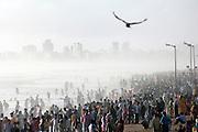 Mumbai locals crowd the waterfront at Juhu Beach to welcome the first rains of the monsoon, Mumbai, Maharashtra, India