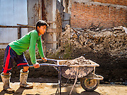 03 MARCH 2017 - BHAKTAPUR, NEPAL: A worker with mud used for mortar waits to drop at a reconstruction in Bhaktapur's Durbur Square. Bhaktapur, a popular tourist destination and one of the most historic cities in Nepal was one of the hardest hit cities in the earthquake. Recovery seems to have barely begun nearly two years after the earthquake of 25 April 2015 that devastated Nepal. In some villages in the Kathmandu valley workers are working by hand to remove ruble and dig out destroyed buildings. About 9,000 people were killed and another 22,000 injured by the earthquake. The epicenter of the earthquake was east of the Gorka district.      PHOTO BY JACK KURTZ
