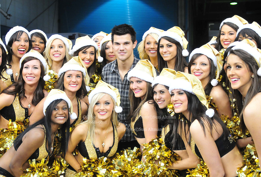 """Twilight ACTOR TAYLOR LAUTNER gets wrapped up by the New Orleans Saints cheerleaders the """" Saintsations""""just before kickoff against the St. Louis Rams Subnday at the Super Dome in NEw Orkeans.hangs out on the Saints sidelines and poses with Saints owner Rita Benson Leblanc  prior to the kick off against the St. Louis Ram.The New Orleans Saints play the St. Louis rams in New Orleans at the Super Dome Sunday Dec. 12,2010. Saints went on to win 31-13. Photo©SuziAltman. New Orleans, Louisiana, U.S. - Twilight Actor TAYLOR LAUTNER hangs out on the Saints sidelines prior to the kick off against the St. Louis Ram.The New Orleans Saints play the St. Louis rams in New Orleans at the Super Dome Sunday Dec. 12,2010. Saints went on to win 31-13..(Credit Image: © Suzi Singer and actress MILEY CYRUS poses for a fan's camera phone with New Orleans police officers on the sidelines prior to The New Orleans Saints' kickoff against the St. Louis Rams at the Superdome. Cyrus is currently filming ''So Undercover'' in New Orleans.Photo©Suzi Altman Twilight series ACTOR TAYLOR LAUTNER  wears a headset and listens as the plays are being called on the New Orleans Sainst sidelines during the game against the St. Louis Rams. LAUTNER and poses with Saints owner Rita Benson Leblanc  prior to the kick off against the St. Louis Ram.The New Orleans Saints play the St. Louis rams in New Orleans at the Super Dome Sunday Dec. 12,2010. Saints won 31-13.Photo©SuziAltman. New Orleans, Louisiana, U.S. - Twilight Actor TAYLOR LAUTNER hangs out on the Saints sidelines prior to the kick off against the St. Louis Ram.The New Orleans Saints play the St. Louis rams in New Orleans at the Super Dome Sunday Dec. 12,2010. Saints went on to win 31-13.Photo©Suzi Altman"""
