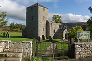 An exterior of St. John the Baptist Church in Edlingham with its fortified belfry to repel cross-border rievers, on 28th September 2017, Northumberland, England. St. John the Baptist Church is a Mediaeval 11th century Church in Edlingham, Alnwick, Northumberland, England. The church is mostly Norman, from two periods, the late 11th - early 12th Century and late 12th century. The church is adjacent to Edlingham Castle, a 13th-century castle with 16th-century battlements and defences.
