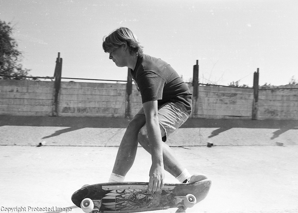 Brian Hulse skateboards in a concrete drainage control ditch in the Tule River in Porterville, California during the fall of 1989.