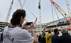 """Fans take pictures of the construction site of the new stadium before the Premier League match at White Hart Lane, London. PRESS ASSOCIATION Photo. Picture date: Saturday April 15, 2017. See PA story SOCCER Tottenham. Photo credit should read: Victoria Jones/PA Wire. RESTRICTIONS: EDITORIAL USE ONLY No use with unauthorised audio, video, data, fixture lists, club/league logos or """"live"""" services. Online in-match use limited to 75 images, no video emulation. No use in betting, games or single club/league/player publications."""