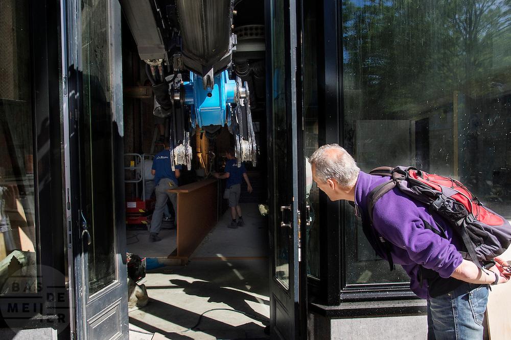 Een man kijkt nieuwsgierig om het hoekje naar de verrichtingen bij een verbouwing. In Utrecht wordt met een zogenaamde Palfingerkraan een grote profielbalk in een bedrijfspand gebracht. Op de plek van de winkel zat eerder het kraakpand Ubica. De kraan is een door Palfinger ontworpen speciale autolaadkraan die compact kan worden opgevouwen en een groot bereik en hefvermogen heeft.<br /> <br /> In Utrecht a huge beam profile is hoisted in a shop with so called Palfinger crane. The crane is a special by Palfinger designed loader crane which can be folded compact for transportation and can handle a big load.