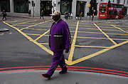 Pedestrian in stripy suit strides past a yellow box junction grid in a City of London street.