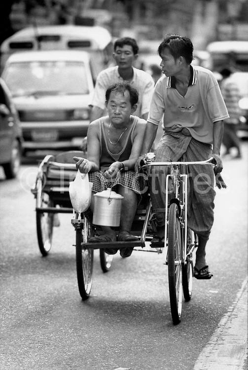 Man with a carrier bag with his shopping in one hand and his lunch in the other travels by cycle rickshaw. Rangoon, Burma 1999