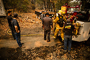 Local civilians work to defend homes threatened by the Glass Fire in Napa Valley, CA on September 29, 2020. Teams of locals have banded together to assist fire fighters and defend homes as the wildfire remains at 0% containment since it began three days ago and now threatens more than 10,000 structures.