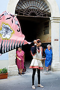 Local women watch members of the Corso Contrada in livery costume at traditional parade in Asciano, inTuscany, Italy