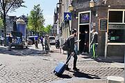 Nederland, Amsterdam, 6-5-2020 Een man met een rolkoffer . Per 1 juni mogen de cafes en andere horeca weer open en bedienen op terrassen voor 30 mensen en met anderhalve meter tussenruimte . De horeca is al enkele weken gesloten vanwege de coronadreiging maar de regering laat het normale dagelijks leven weer langzaam opstarten . Door de afwezigheid van toeristen is het ongewoon rustig op de wallen en de rest van de binnenstad van Amsterdam .  Unlock,beperkende,beperkingen, opheffen,versoepelen,versoepeling , opengooien, massatoerisme,toeristisch, toeristische, airbnb, toerist . Foto: Flip Franssen