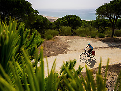 Elevated view of woman biker riding on dirt track near sea