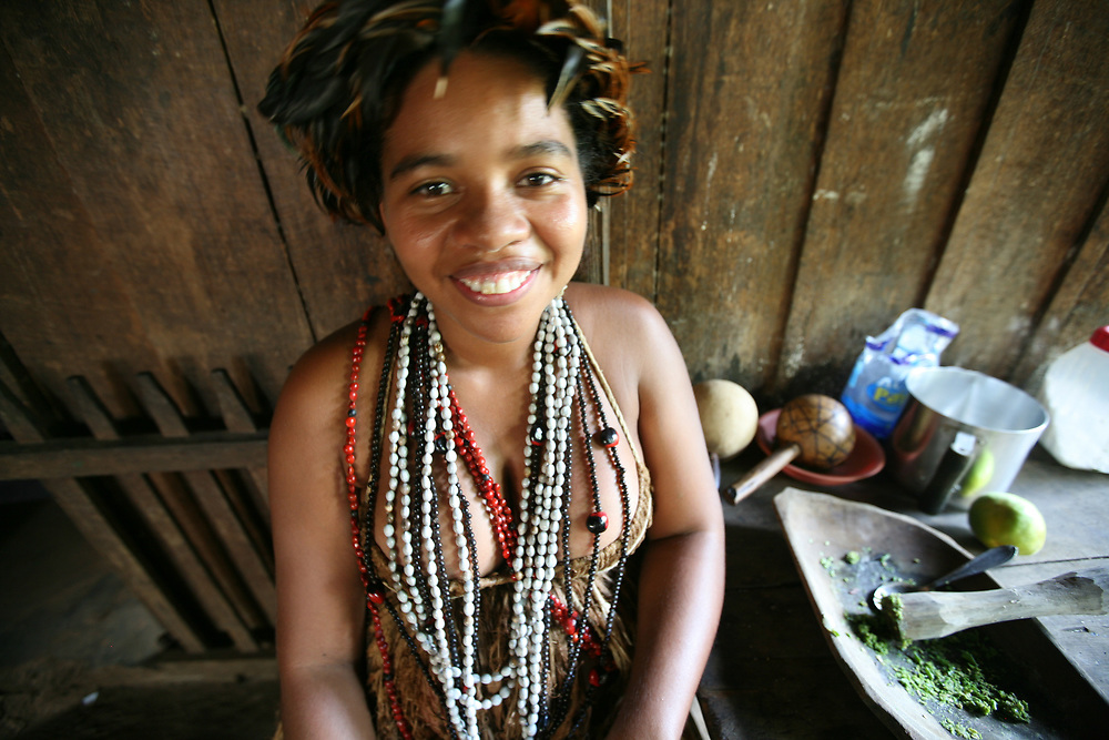 People of the Tupinambá tribe paint themselves with genipapo juice which is a natural ink that darkens slowly. Genipapo is also prepared as a juice to drink, which is effective against bronchitis. The facepaint is of a puma's teeth and whiskers. The women wear a feather headdress, a bark dress and beads.