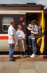 Mother and father saying goodbye to teenage son getting on train,