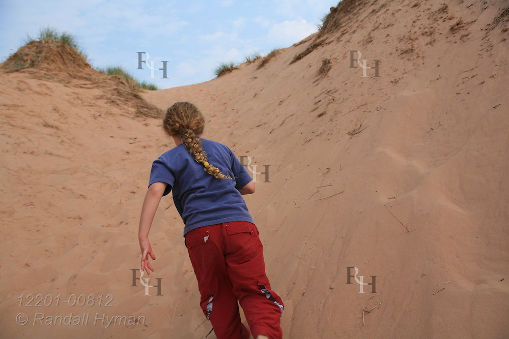 Young girl with braid runs up sand dune at Pictured Rocks National Lakeshore, Michigan.
