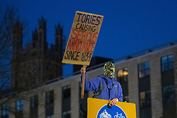 © Licensed to London News Pictures. 03/04/2021. Bristol, UK. A protester wearing a balaclava stands on a street sign holding an anti Tori placard during the 'Kill the Bill' demonstration in Bristol. Crowds gathered to protest against the proposed Police, Crime, Sentencing and Courts Bill. Photo credit: Peter Manning/LNP