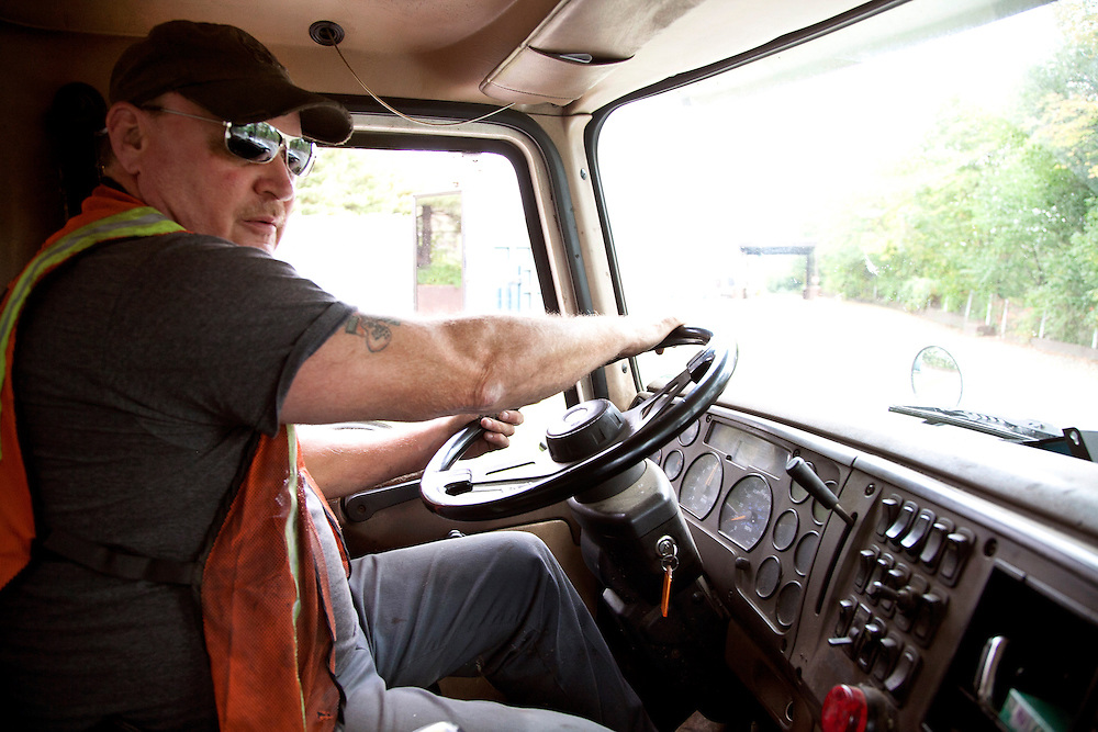 Waste Paper Recycle trucker driving in cab of truck