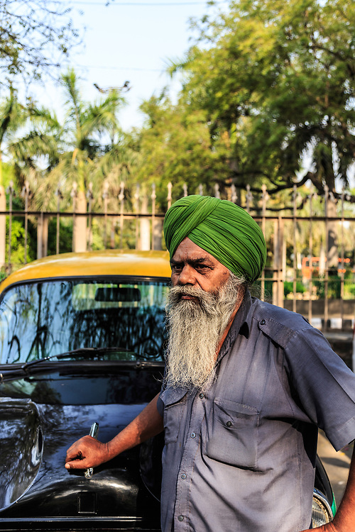 A taxi driver with his old Hindustan Ambassador  automobile in New Delhi, India. In 2014, after 50 years production, road ended for India's iconic Ambassador car.  Today older models are  highly collectible.
