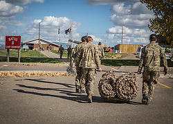© Licensed to London News Pictures. 08/10/2014.  British Army Training Unit Suffield (BATUS), Canada. A group of soldiers carry equipment back to the stores as the exercise comes to an end.  The troops will have spent 26 days out on the prairie.<br /> <br /> BATUS has been home to the Army for the past 42 years .  It is the only place where all elements of the British Army train together for war.  The soldiers are put to test on everything from armoured vehicles to infantry tactics.        Photo credit : Alison Baskerville/LNP
