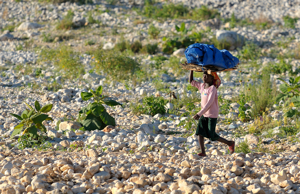 A girl carries a bundle on her head to the morning market in Lastic le Roche, Haiti.