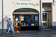 A woman walks past the Wadebridge Renewable Energy Network (WREN) energy shop in Wadebridge, North Cornwall, UK. The shop is the focal point for WREN activities which aims to turn the area into the first renewable energy town.