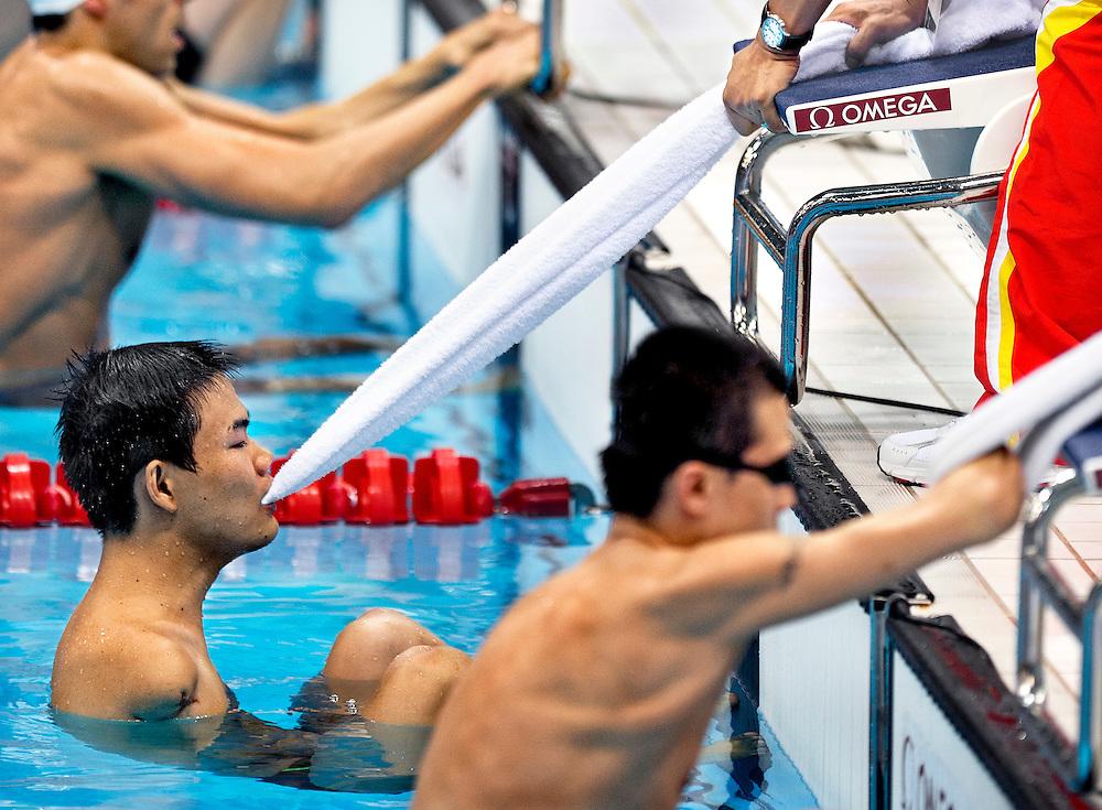Engeland, Londen, 30-08-2012.<br /> Paralympische Spelen.<br /> Zwemmen, 100 meter rugslag, Klasse S6, Mannen.<br /> Tao Zheng uit China hangt bij de start met zijn mond aan de handdoek die een verzorger vasthoudt omdat hij geen armen heeft. Hij zal goud winnen in een nieuw wereldrecord van 1:13.56.<br /> Foto : Klaas Jan van der Weij