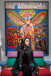 """© Licensed to London News Pictures. 01/11/2016. London, UK. A staff member sits in front of """"Ewigkeitendegottt, Sein Engel"""" by August Walla, est. GBP6-8k. The first look of """"Bowie / Collector"""", artworks from the late David Bowie's personal art collection, ahead of their sale later this month at Sotheby's. Photo credit : Stephen Chung/LNP"""